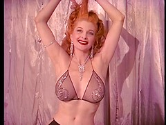 Sexy redhead retro stripteaser posing before camera