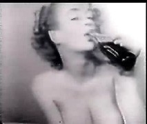 Topless vintage beauty models her stunning breasts and enjoys a soda pop